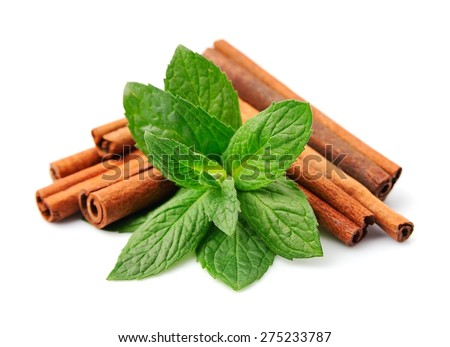 Sticks of cinnamon with mint on a white background