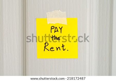 sticky note write a message pay the rent on wood door background