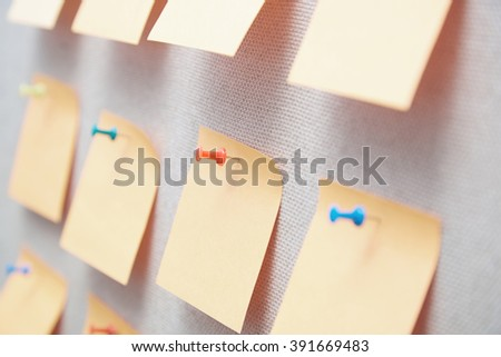 Sticky notes on a bulletin board. Close-up view