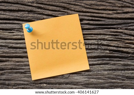 sticky paper note holding by pin on the old wooden background
