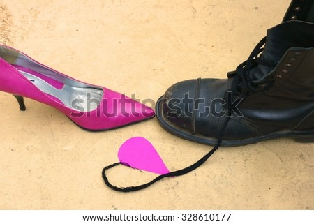 Stiletto heels woman's shoe and a man's boot - opposites attract when it comes to love concept, happy valentine's day