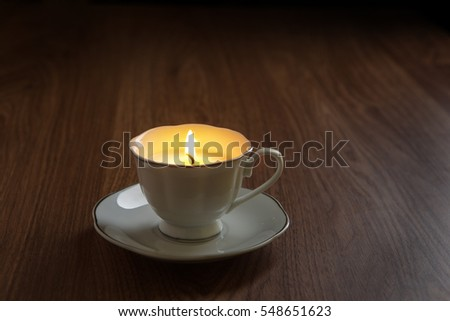 still life image of a candle made in teacups