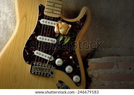 Still life music love valentines concept on vintage solid wood body electric guitar with pale rose over grunge