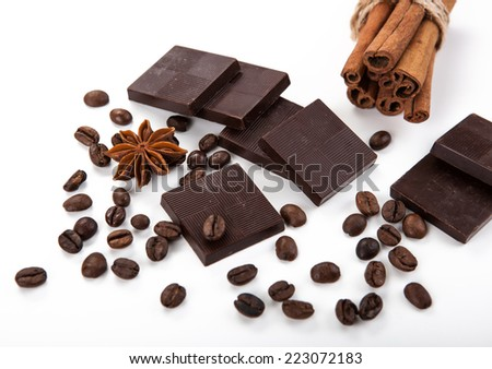 still life of chocolate bars, cinnamon and coffee beans on white