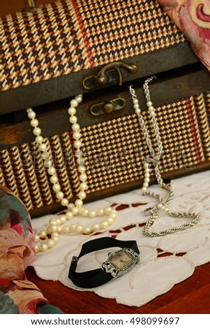 Still life of vintage jewellery in old fashioned plaid box.  Focus is on beautiful vintage watch in foreground.
