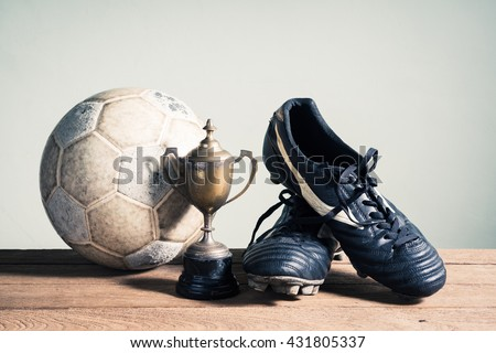 still life photography : old football, football shoes and trophy on old wood table in championship concept