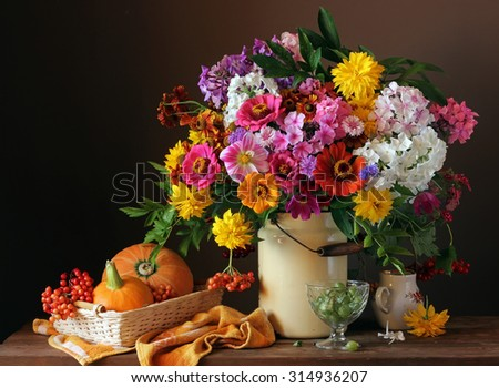 Still life with a bouquet of cultivated flowers, pumpkins and berries. Autumn still life.