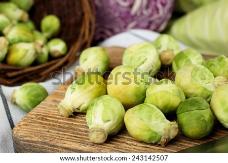 Still life with assortment cabbages on cutting board on wooden background