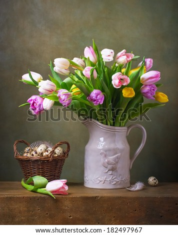 Still life with colorful tulips and quail eggs