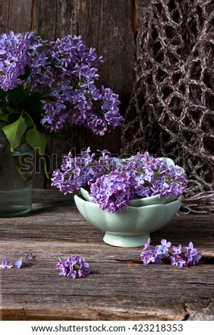 Still life with lilac flowers on wooden background