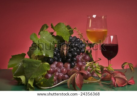 Still-life with multicolor grapes and red wine glasses
