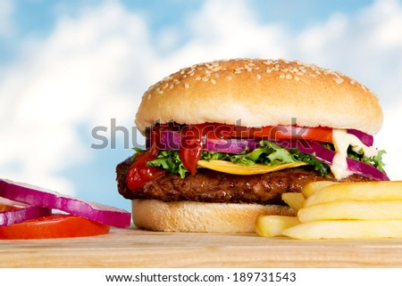 Stock image of cheeseburger with fries outdoors on wooden plate