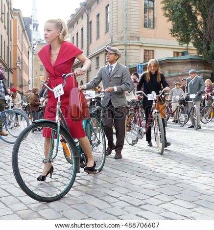 STOCKHOLM - SEPT 24, 2016: Beautiful woman dressed in old fashioned red dress cycling in the Bike in Tweed event September 24, 2016 in Stockholm, Sweden