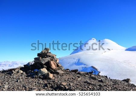 stone cairn at the mountain top on the background of mount Kazbek