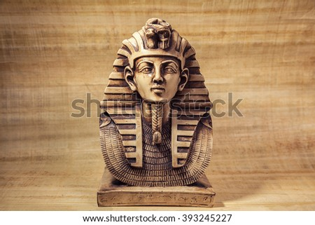Stone pharaoh tutankhamen mask on papyrus background