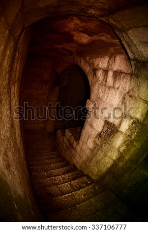 Stone stairway to the darkness of dungeon of a medieval castle