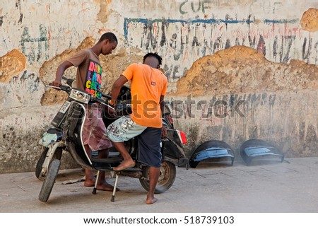 STONE TOWN, ZANZIBAR, TANZANIA - OCTOBER 29, 2014: Unidentified men working on a scooter (motorcycle) in a narrow alley of the historical Stone Town