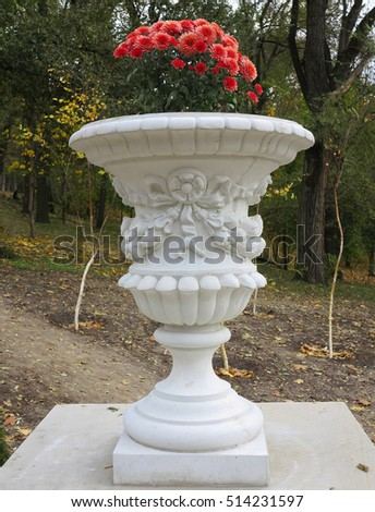 Stone vase in the old classical style with flowers in the park .
