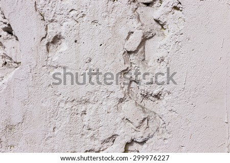 Stone wall background with cracked paint and holes