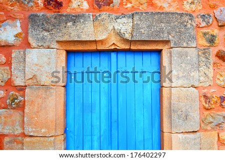 Stone wall with a closed blue door.