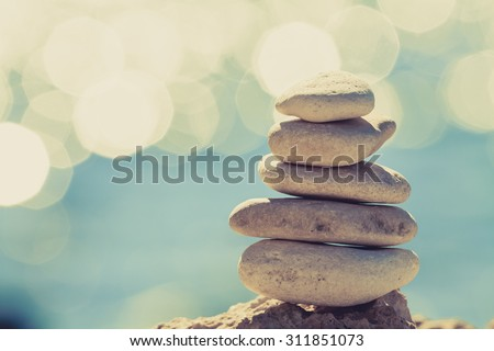 Stones balance at the vintage beach, inspirational summer landscape. Stability hierarchy stack over blue sea in Croatia. Spa or well-being, freedom and stability concept on rocks.