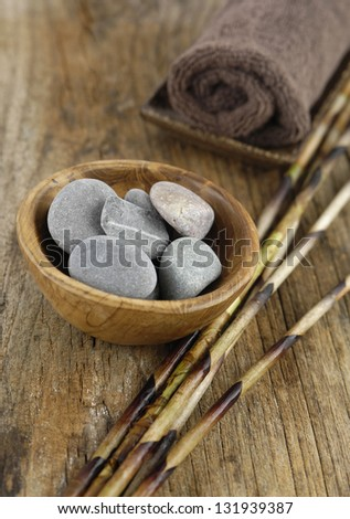 stones in bowl, towel ,dry bamboo grove on old wood