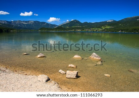 Stones in clear water of mountain lake with the Alps in the background, Hallstattersee, Upper Austria