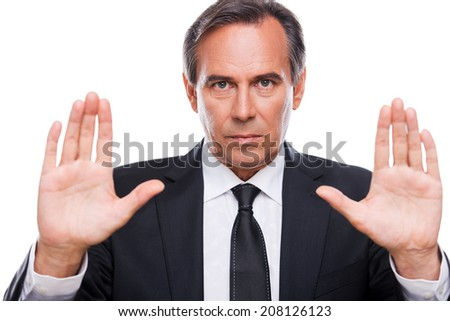 Stop it! Serious mature man in formalwear looking at camera and showing his palms while standing isolated on white background