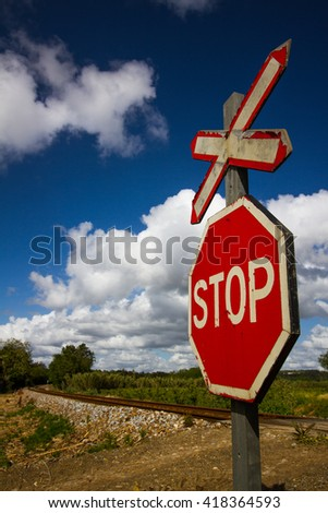 Stop sign on a railway crossroad during a sunny cloudy day