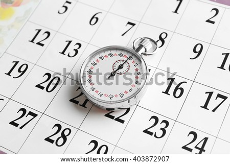 Stopwatch on calendar background, close up