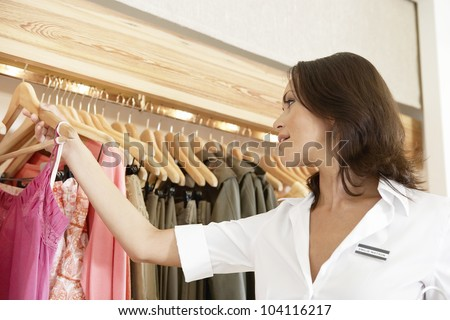 Store assistant sorting clothes on store's rails, close up.