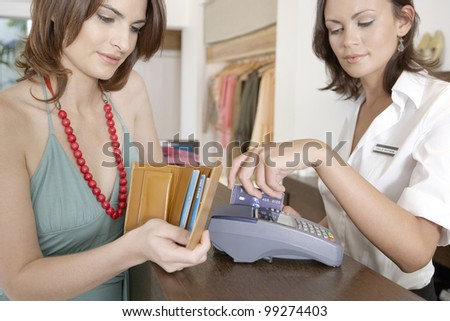 Store attendant sweeping the client's credit card in a card reader.