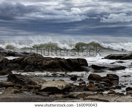 Storm waves crashing on rocks under a dramatic sky