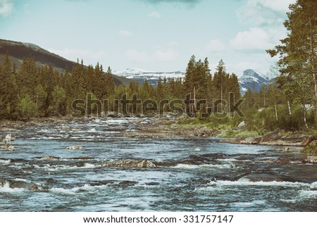 stormy mountain river on a background of snowy mountains, Norway