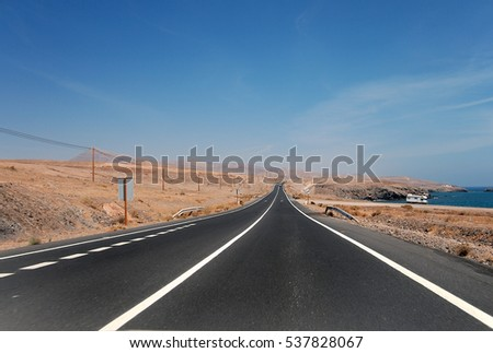 Straight asphalt highway goes beyond the horizon between volcanic sandy hills and mountains. Against of deep blue sky background. Fuerteventura, Canary Islands, Spain