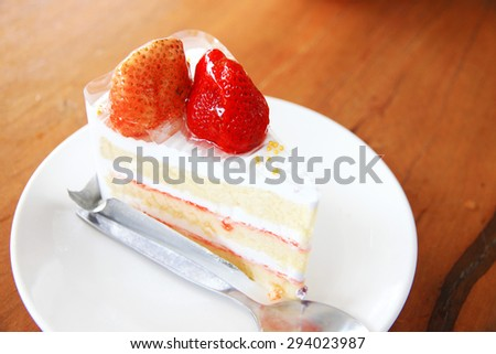 Strawberry cake on wooden table background.