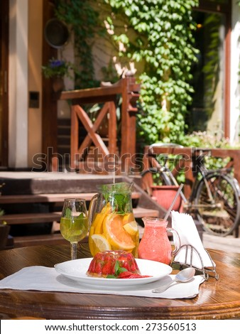 strawberry desserts and jar of sangria served on the summer terrace