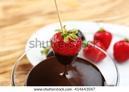 Strawberry dipping into bowl with chocolate on blurred background