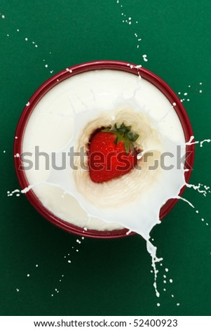 Strawberry dropped into bowl of milk, creating a splash sculpture