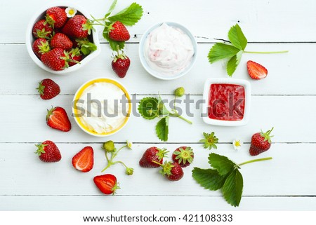 strawberry fruits with jam and whipped cream dessert on white wood table background