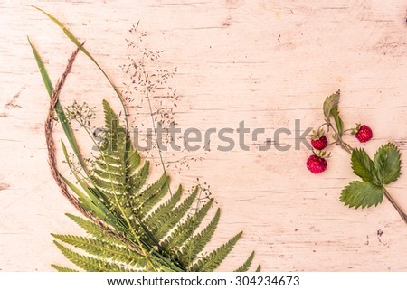 Strawberry with ferns on old wooden table. Image in the orange-purple toning