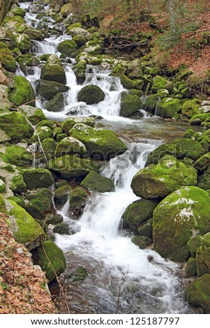 Stream in the forest, waterfalls and stones covered in green moss