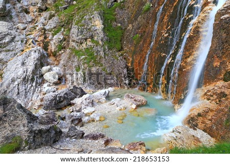 Streams of water falling into small blue pond, Lasties valley, Sella massif, Dolomite Alps, Italy
