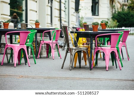 Street cafe. Europe. Cloudy weather is cold. On the chairs are blankets and pillows.