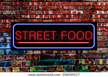 Street Food Neon sign on a Graffiti. Bricks wall