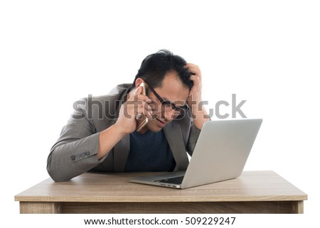 Stressed businessman talking on phone work  with laptop sitting at table isolated on white background.