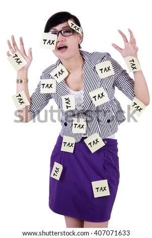 Stressful businesswoman with paper notes attached on her body to remind tax time
