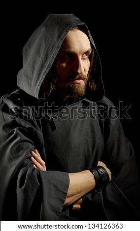 strict monk in cape, black background