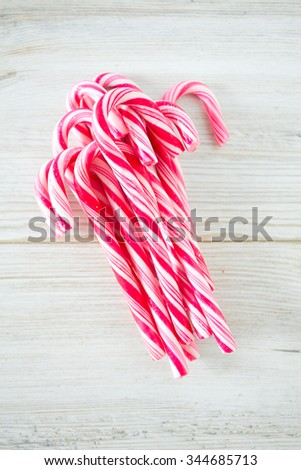 Striped Christmas candies on wooden surface