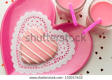 Striped pink heart cookie on pink plate with glasses of strawberry milk